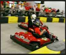 Go kart racing down a straight away on the kart track.